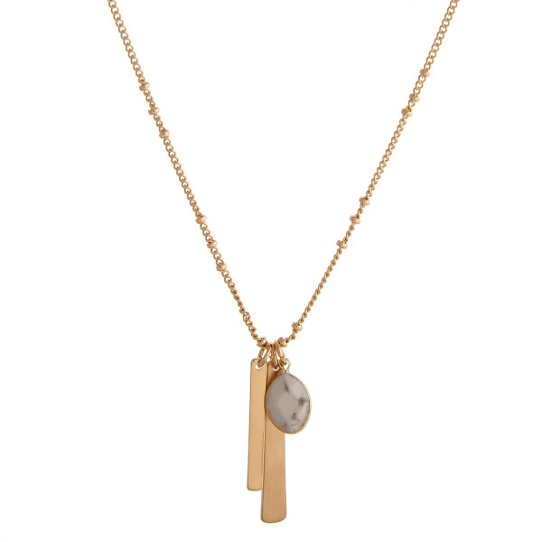 "Dainty satellite chain necklace featuring a natural stone and metal tassel accents. Approximately 18"" in length."