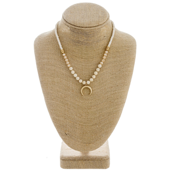 "Natural stone beaded necklace featuring a crescent detail and gold accents. Approximately 16"" in length."