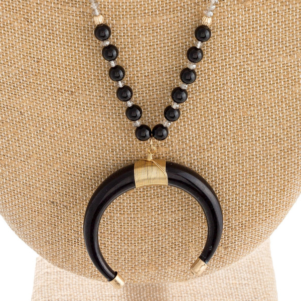 """Long beaded necklace featuring a resin crescent pendant with wire wrapped details. Pendant approximately 2"""". Approximately 36"""" in length overall."""