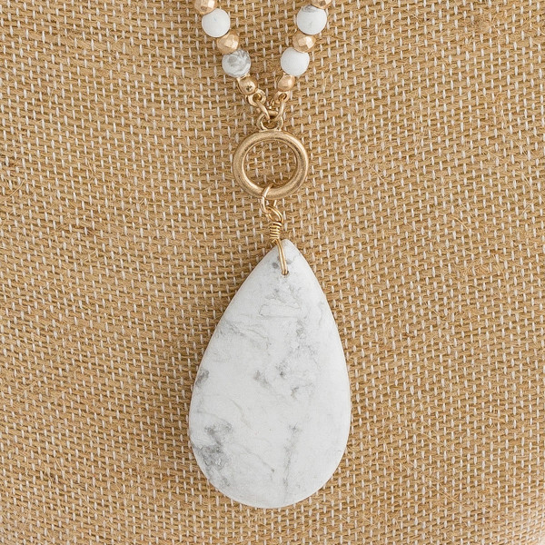 "Iridescent, natural stone and gold beaded necklace featuring a natural stone teardrop inspired pendant. Pendant approximately 2"". Approximately 40"" in length overall."