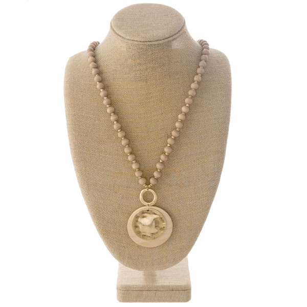 "Long wood beaded necklace featuring a wood inspired disc pendant with a metal disc accent. Pendant approximately 3.5"". Approximately 40"" in length overall."
