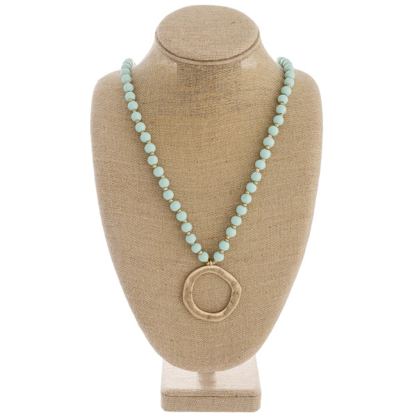 """Long wood beaded necklace featuring a metal circular pendant. Pendant approximately 2"""" in diameter. Approximately 38"""" in length overall."""