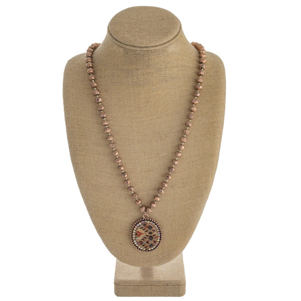 """Long faceted beaded necklace featuring a metal pendant with cork and western inspired details and rhinestone accents. Pendant 2"""". Approximately 36"""" in length overall."""