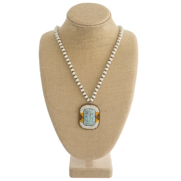 """Long beaded necklace featuring a natural stone pendant with seed beaded accents. Pendant approximately 2.5"""". Approximately 34"""" in length overall."""