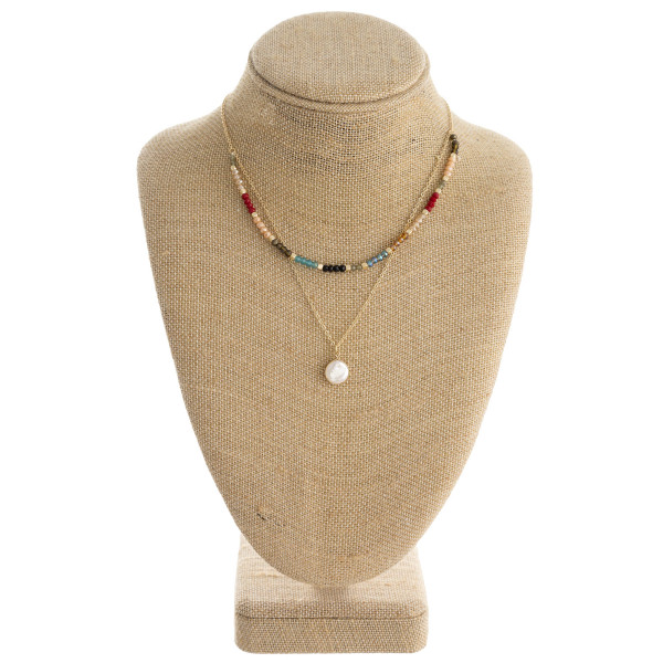 "Dainty cable chain necklace featuring a double layered beaded bib pendant with a pearl accent. Approximately 16"" in length."
