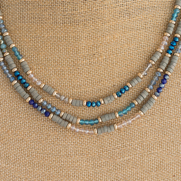 "Trio layered beaded necklace featuring wood, iridescent and faceted bead details. Approximately 16"" in length."