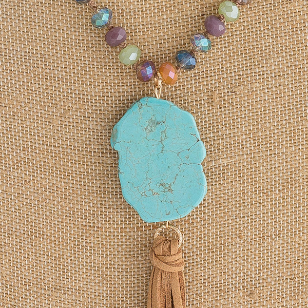"Long faceted beaded necklace featuring a natural stone and tassel pendant. Approximately 42"" in length."