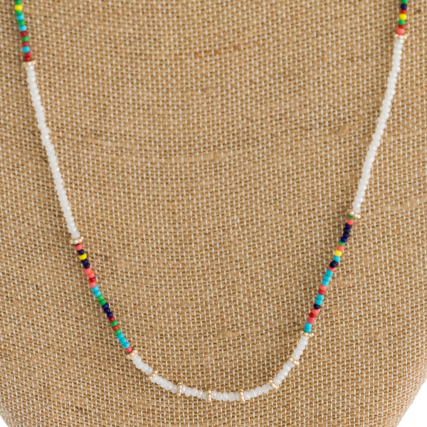 "Long dainty link bar seed beaded necklace with flower bead accents. Approximately 36"" in length."