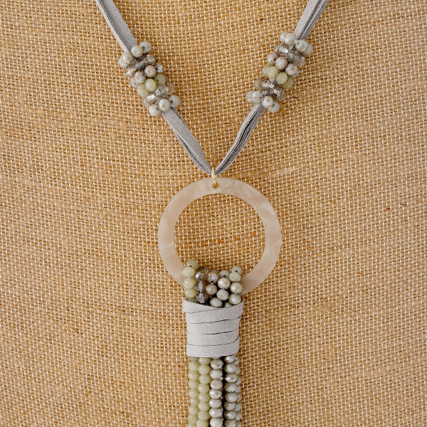 "Faux leather necklace featuring a faceted beaded tassel detail with a resin accent. Pendant approximately 6"". Approximately 38"" in length overall."