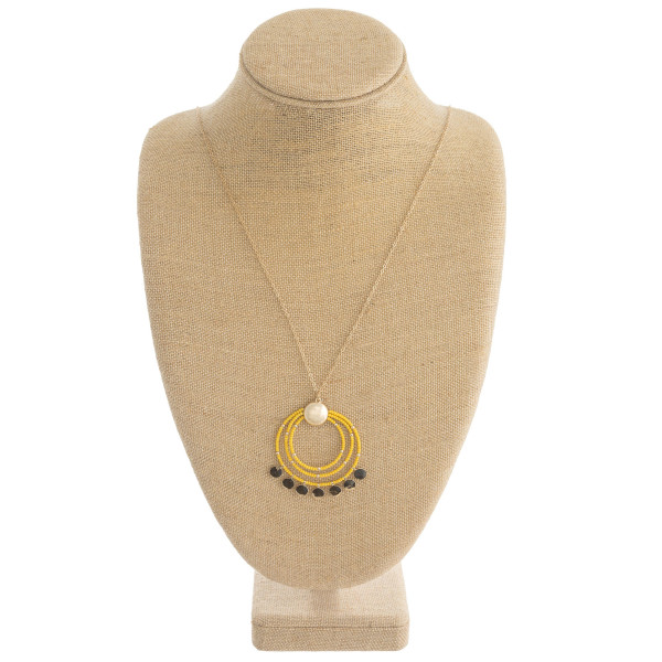 "Long dainty chain necklace featuring a seed beaded nested circle pendant with gold disc accents. Pendant approximately 2"" in diameter. Approximately 38"" in length overall."