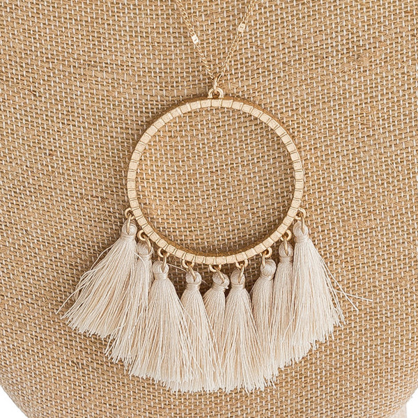 "Long dainty chain necklace featuring a circular pendant with fanned tassel details. Pendant approximately 3"". Approximately 36"" in length overall."