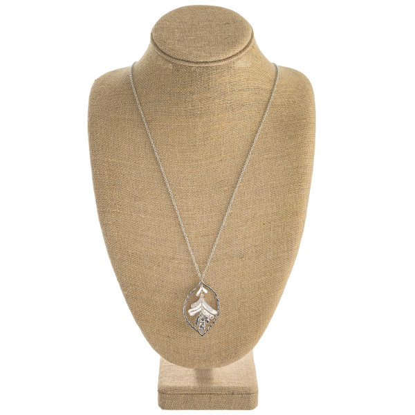 """Long rolo chain necklace featuring a nested leaf inspired pendant. Pendant approximately 2.5"""". Approximately 36"""" in length overall."""