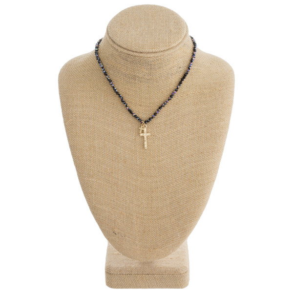 "Short beaded necklace featuring a cross pendant. Pendant approximately 1"" in length. Approximately 16"" in length overall."