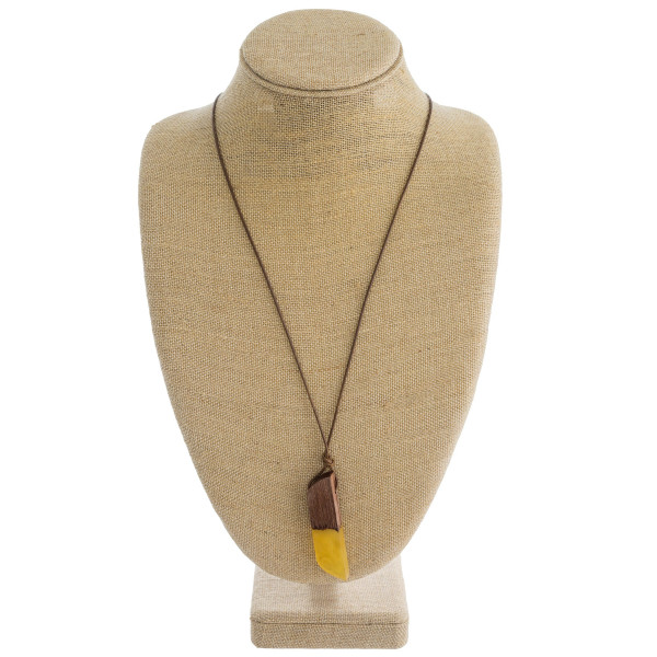 """Long faux leather cord necklace featuring a resin and wood inspired pendant. Pendant approximately 3"""". Approximately 34"""" in length overall."""