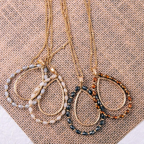 """Long satellite chain necklace featuring a nested teardrop pendant with oval faceted beaded details. Pendant approximately 2"""" in length. Approximately 34"""" in length overall."""