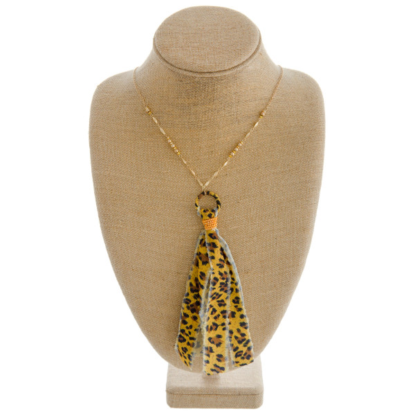 """Long leopard print fabric tassel pendant necklace with beaded accents. Pendant approximately 7"""" in length. Approximately 44"""" in length overall."""