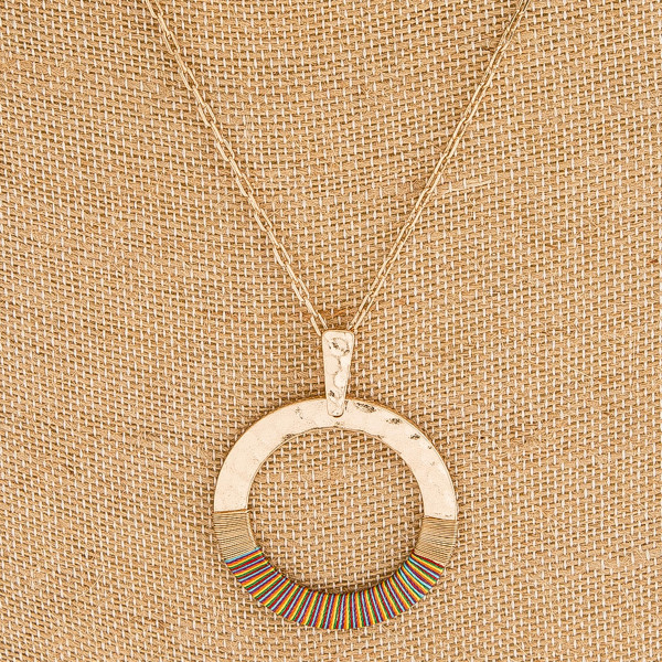 "Hammered metal thread wrapped open circle pendant necklace. Pendant approximately 1.5"" in diameter. Approximately 34"" in length overall."