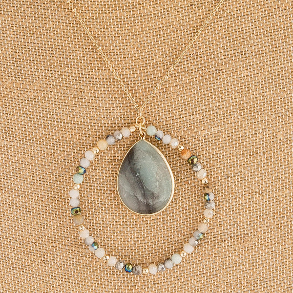 "Long semi precious nested pendant necklace with beaded details. Pendant approximately 2.5"" in diameter. Approximately 36"" in length overall."