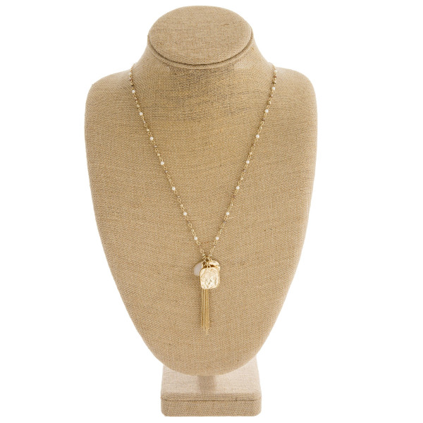 """Long beaded necklace featuring a chain linked charm tassel pendant with pearl accents. Pendant approximately 3"""" in length. Approximately 36"""" in length overall."""