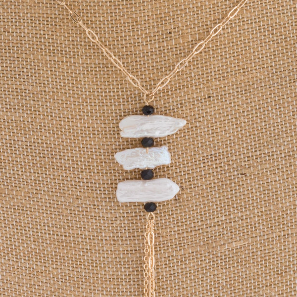 """Long pearl accented necklace featuring a chain link tassel. Approximately 41"""" in length."""