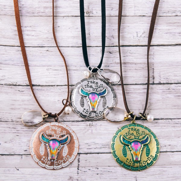 """Brown faux leather necklace featuring a patina bull pendant with """"Take the bull by the horns"""" engraved details and crystal accent.  - Pendant approximately 2.25"""" in diameter - Approximately 38"""" in length overall with 3.5"""" extender"""