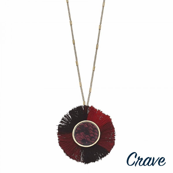 """Long metal encased faux leather snakeskin round pendant necklace featuring color block tassel accents. Pendant approximately 2"""" in diameter. Approximately 34"""" in length overall."""