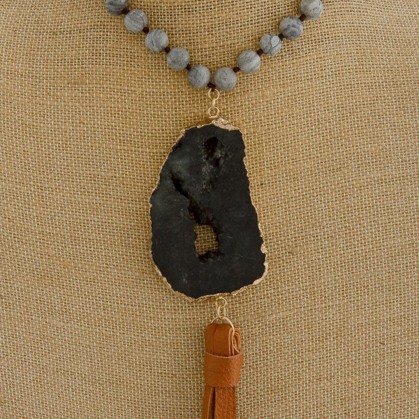 "Semi precious beaded faux leather necklace featuring a druzy tassel pendant. Pendant approximately 8.5"" in length. Approximately 44"" in length overall."