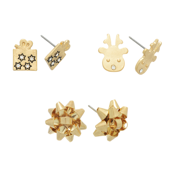 Worn gold tone set of three post earrings featuring a gift, a reindeer, and a gift bow.