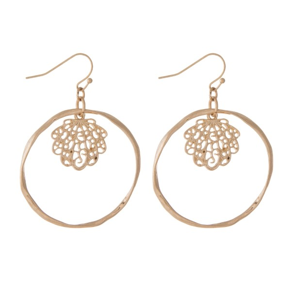 "Gold tone fishhook earrings with a hammered circle and a filigree seashell. Approximately 1.25"" in diameter."