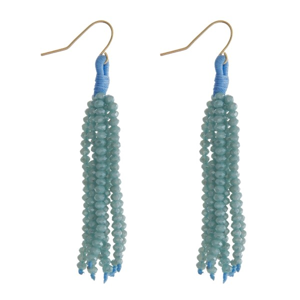 "Gold tone fishhook earrings with a light blue beaded tassel. Approximately 2.5"" in length."