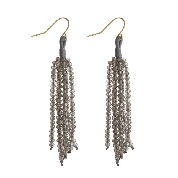 "Gold tone fishhook earrings with a gray beaded tassel. Approximately 2.5"" in length."