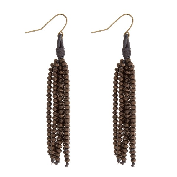 "Gold tone fishhook earrings with a hematite beaded tassel. Approximately 2.5"" in length."