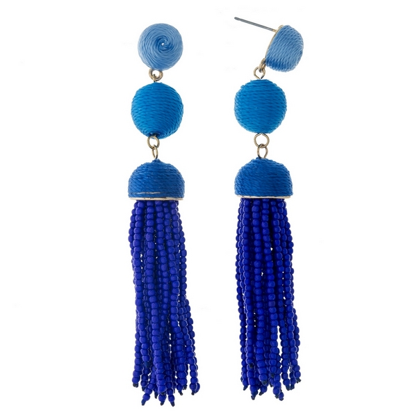 "Gold tone stud earrings with blue ombre thread wrapped beads and a blue tassel. Approximately 3.5"" in length."