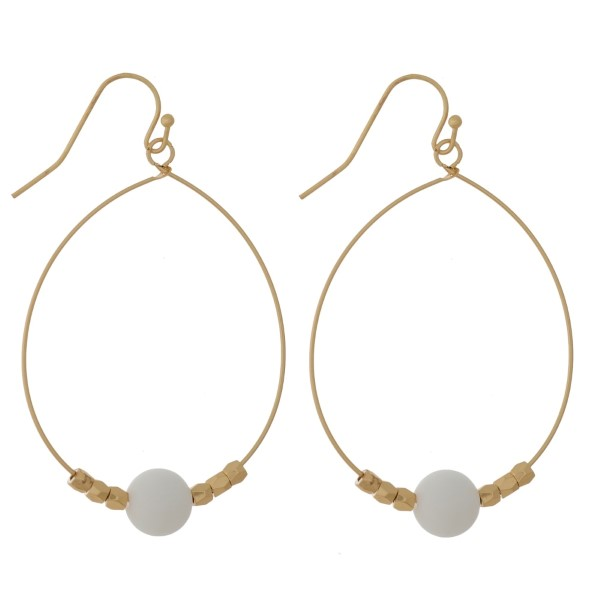"""Gold tone fishhook earrings with an oval shape and a natural stone bead. Approximately 2.25"""" in length. Natural stone colors may vary."""