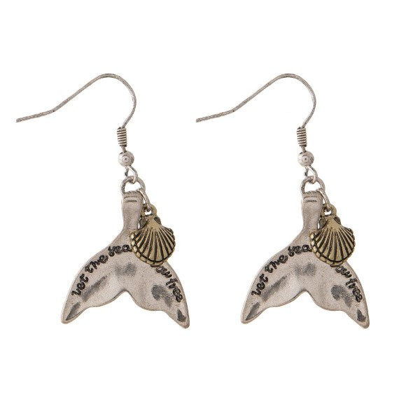 "Silver tone fishhook earring stamped with Let the Sea Set Your Free and accented with a sea life charm. Approximately 1.5"" in length."