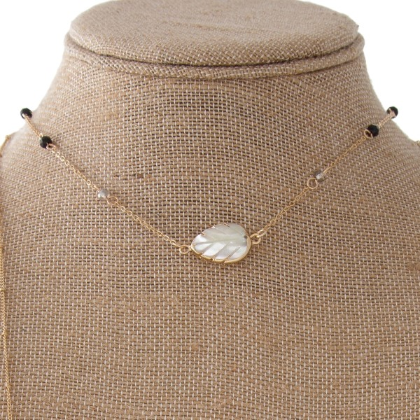 "Layered necklace with faceted beads and natural shell leaf accent. Approximately 16""-32"" in length."