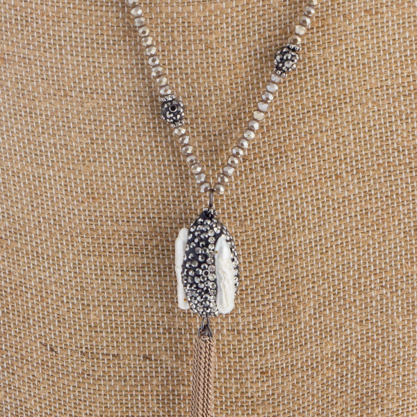 """Long beaded necklace with rhinestone pendant details and  tassel. Approximate 40"""" in length."""