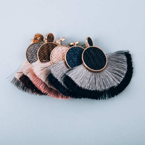 "Long metal earrings with woven raffia details and soft tassels. Approximately 2.5"" in length."