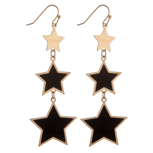 "Drop metal earrings featuring black and gold star accents. Approximately 2.75"" in length."