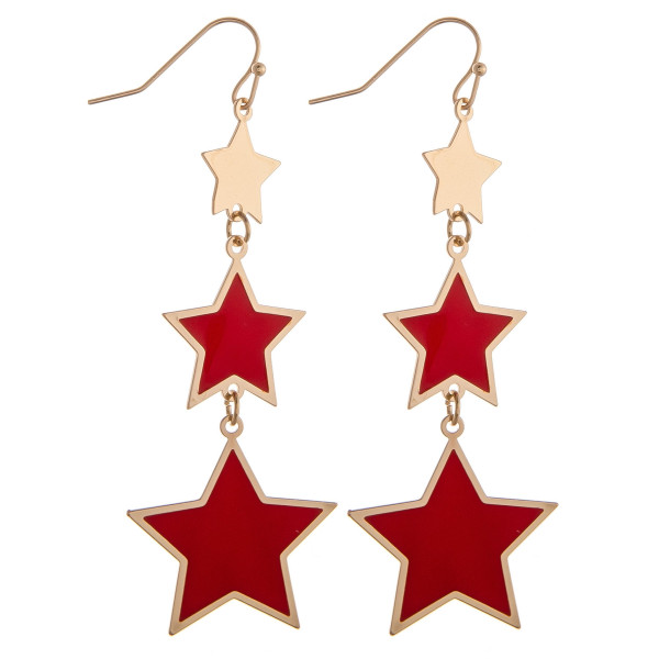 "Drop metal earrings featuring red and gold star accents. Approximately 2.75"" in length."