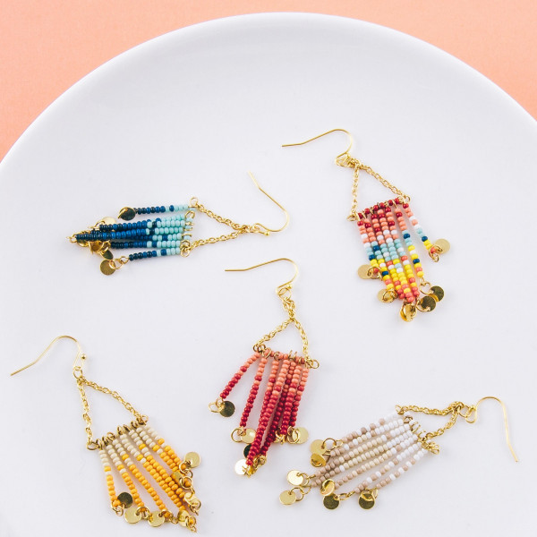 "Long drop earrings featuring beaded tassel details with gold disc accents. Approximately 3"" in length."