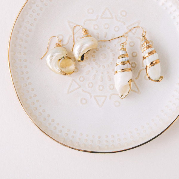 "Seashell inspired drop earrings featuring gold accents. Approximately 1"" in diameter."