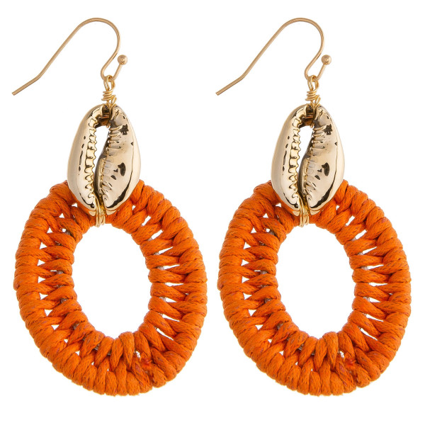 "Long rattan wrapped earrings featuring a gold puka shell detail. Approximately 2"" in length."