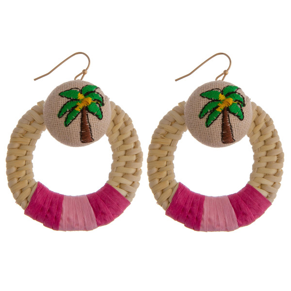 "Circular woven rattan earrings featuring a palm tree detail and hot pink accent. Measure approximately 2"" in diameter."