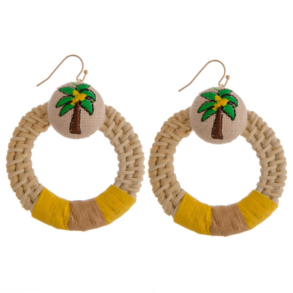 "Circular woven rattan earrings featuring a palm tree detail and yellow accent. Measure approximately 2"" in diameter."