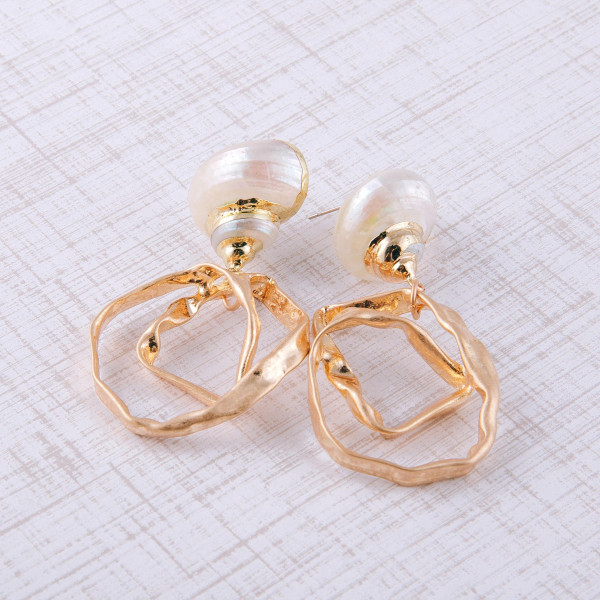"Gold metal earrings featuring a twisted detail and a sea shell stud accent. Approximately 2.5"" in length."