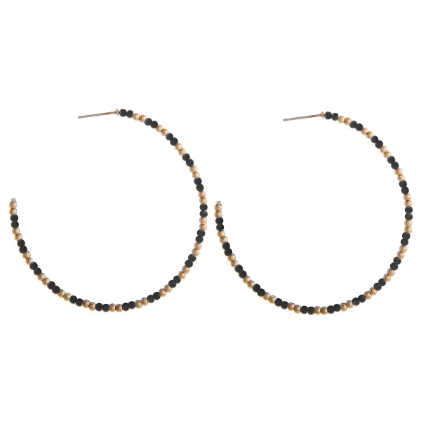 "Large black beaded hoop earrings featuring gold accents. Measures approximately 2.5"" in diameter."