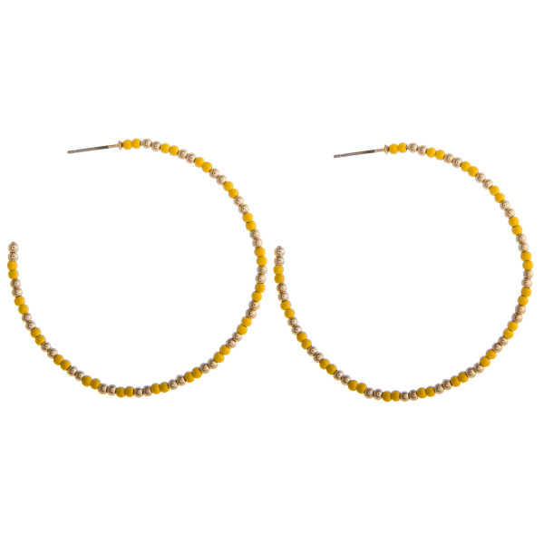 "Large yellow beaded hoop earrings featuring gold accents. Measures approximately 2.5"" in diameter."