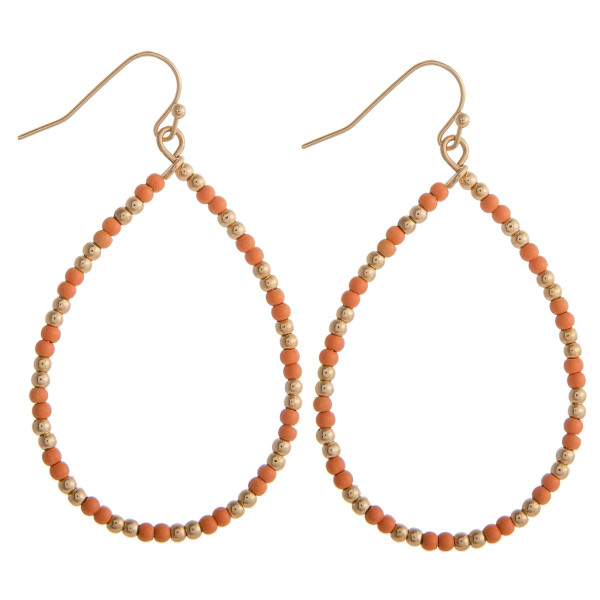 """Coral beaded teardrop earrings featuring gold accents. Measures approximately 2"""" in diameter."""