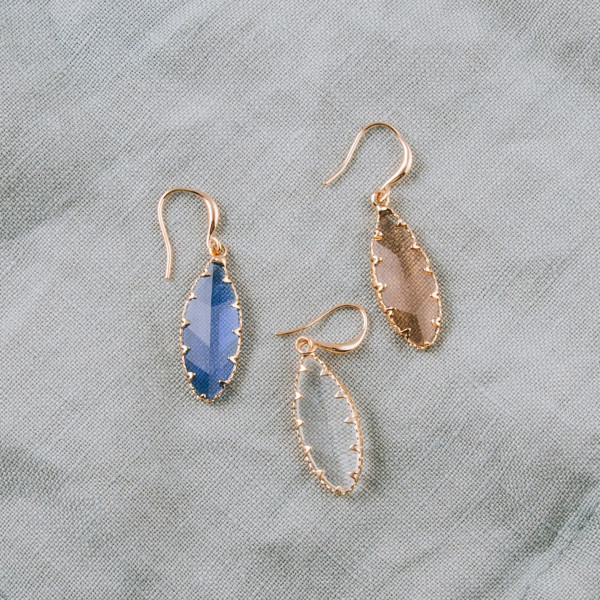 "Dainty earrings featuring an iridescent stone and gold metal accents. Approximately 1"" in length."